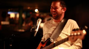 Smiley photo at Midtones with white shirt and jazz bass